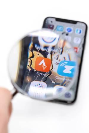 Blick durch Lupe auf Strava App auf schwarzem Mobiltelefon vor weißem Hintergrund