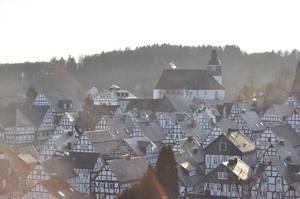 Blick über die Dächer von weißen Fachwerkhäusern auf Kirche des Dorfs Freudenberg
