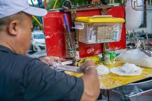 Blick über Schulter eines Mannes bei Zubereitung des typisch vietnamesischen Desserts Bo Bia in Vietnam