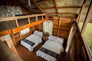 Blick von der oberen Etage auf das Schlafzimmer eines hübschen kleinen Holzchalets