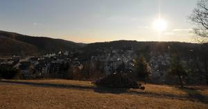 Blick von Hügel über Dorf Freudenberg mit vielen Fachwerkhäusern gegen Sonne fotografiert
