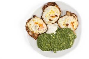 Blick von oben auf angerichteten Teller mit gebratenen Eiern und Rahmspinat