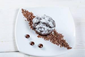 Blick von oben auf appetitlich angerichteten Nachtisch mit Schokolade und Puderzucker