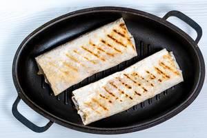 Blick von oben auf Bratpfanne mit zwei gebratenen Shawarma auf weißem Küchentisch