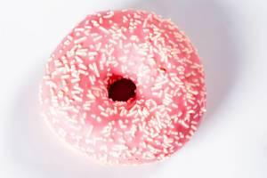 Blick von oben auf Donut mit pinkfarbener Glasur und weißen Streuseln vor weißem Hintergrund