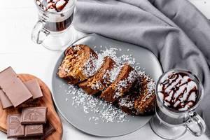 Blick von oben auf eine Schweizer Rolle aus Schoko und Kirsche, neben einer zerbrochenen Schokoladentafel und Kaffee mit Sahne
