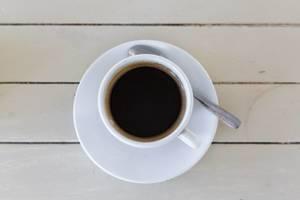 Blick von oben auf eine weiße Tasse gefüllt mit Americano Kaffee auf weißem Holzhintergrund