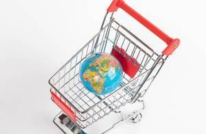 Blick von oben auf Einkaufswagen mit Weltkugel mit farbig hinterlegen Ländern vor weißem Hintergrund