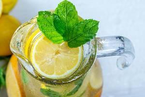 Blick von oben auf frische Limonade in Glaskaraffe mit Zitronenscheibe und frischer Minze