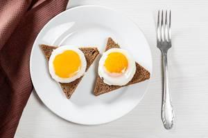 Blick von oben auf Frühstück mit zwei runden Spiegeleiern auf Toast auf weißem Tisch