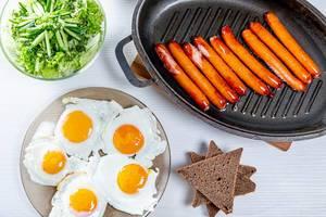 Blick von oben auf Frühstückstisch mit gebratenen Würstchen, Spiegeleiern, Toast und Salat