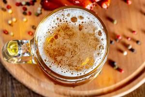 Blick von oben auf gefülltes Bierglas auf Holzbrett mit Chilis und Pfefferkörnern