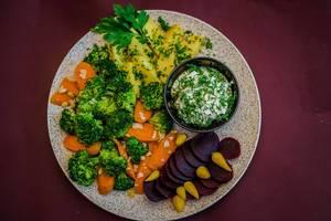 Blick von oben auf Gemüseteller mit roter Bete, Karotten, Kartoffeln und Kräuterquark