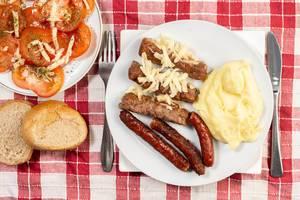 Blick von oben auf Gericht mit Hackfleischwürste, Stampfkartoffeln, knuspriges Brot und Tomaten