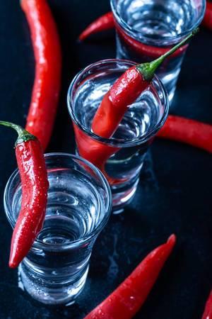 Blick von oben auf Gläser gefüllt mit Wodka und scharfen frischen Chilis auf schwarzem Tisch