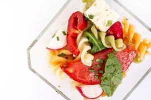 Blick von oben auf Glasschale mit Salat aus Nudeln, eingelegtem Käse, Tomate, Radieschen und Rucola