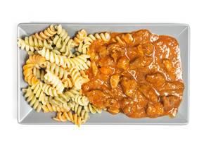 Blick von oben auf hausgemachtes Gulasch mit saftigen Fleischstücken und Fusilli Pasta