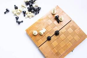 Blick von oben auf hölzernes Schachbrett und Schachfiguren vor weißem Hintergrund