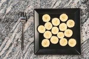 Blick von oben auf in Scheiben geschnittene, aromatische Banane auf eckigem, schwarzem Teller