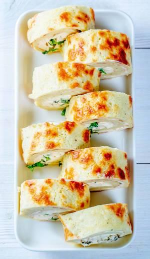 Blick von oben auf in Scheiben geschnittener Pfannkuchen gefüllt mit Käse und Kräutern auf Teller