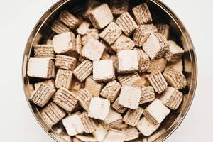 Blick von oben auf kleine Schokoladenwaffeln in Keksdose vor weißem Hintergrund