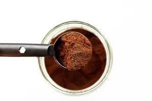 Blick von oben auf Löffel mit fein gemahlenem Kaffeepulver über Glas mit Kaffee vor weißem Hintergrund