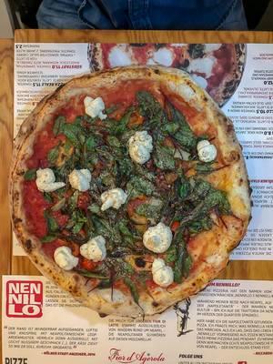 Blick von oben auf reichhaltige Pizza mit Käse und Kräutern auf Tischset mit Menu in Pizzeria