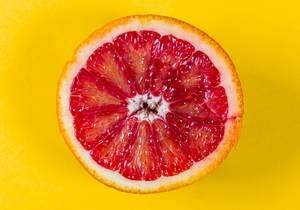 Blick von oben auf saftige halbe Blutorange vor gelbem Hintergrund