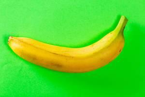 Blick von oben auf sattgelbe Banane vor leuchtend grünem Hintergrund
