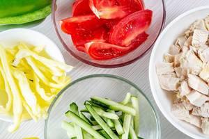Blick von oben auf Schalen mit geschnittenem Gemüse wie Tomaten und Gurken sowie Hähnchen
