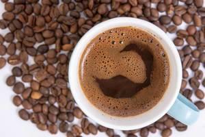 Blick von oben auf Tasse mit aufgebrühtem Kaffee auf Kaffeebohnen auf weißem Tisch