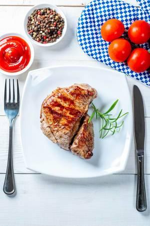 Blick von oben auf Teller mit delikatem Steak neben Tomaten, Pfeffer und Soßentöpfchen und Besteck