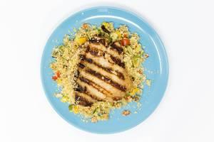 Blick von oben auf Teller mit Hähnchen arabisch gegrillt mit Gemüsecouscous mit Razel Hanout Dip