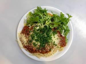 Blick von oben auf Teller Spaghetti mit Tomatensoße, geriebenem Käse, Petersilie und grünem Salat