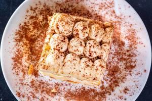 Blick von oben auf Tiramisu-Dessert mit Schokopulver angerichtet auf weißem Teller