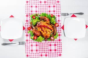 Blick von oben auf Tisch gedeckt für zwei Personen mit Brathähnchen auf Gemüse und Salat