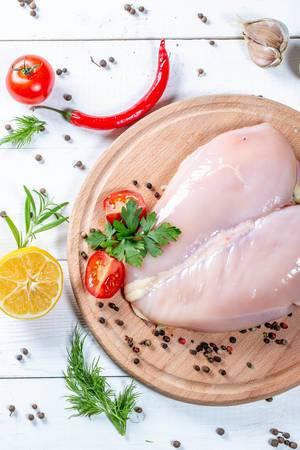 Blick von oben auf ungebratenes Hähnchenfleisch mit aromatischen Zutaten auf weißem Holztisch