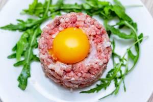 Blick von oben auf weißen Teller mit Tatar (Schabefleisch vom Rind) mit Rucola und rohem Ei