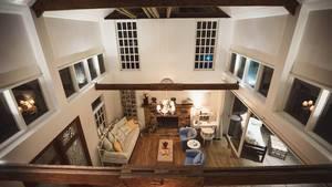 Blick von oberem Stockwerk auf Wohnzimmer mit Kamin, Sofa und Sessel sowie die Gartenterrasse
