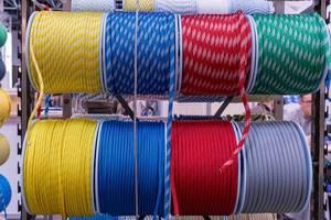 Blick von vorne auf Rollen mit einfarbigen und gemusterten Schiffstauen in verschiedenen Farben