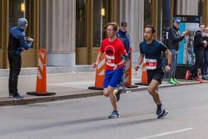 Blind participant at the Chicago Marathon 2019 running next to another athlete. The two hold a cord that connects them