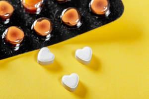 Blister-Packung mit Medikamenten und drei Tabletten in Herzform auf gelbem Hintergrund