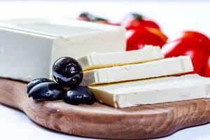 Block und Scheiben Fetakäse mit schwarzen Oliven und Tomaten auf Holzbrett