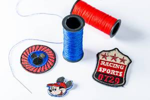 Blue and red thread coils with patches for clothing repair
