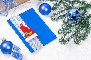 Blue Christmas Card with Christmas Hat and blue spheres and branches