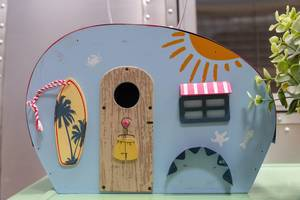 Blue miniature caravan with beach flair, a surfboard and summer painting