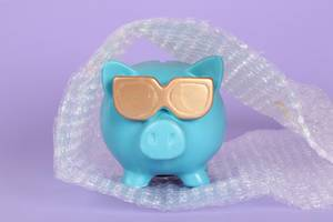 Blue piggy bank packed in bubble wrap