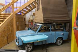 Blue retro car with white roof and brown tent construction on top of the roof