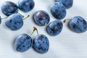 Blue ripe plums on white table