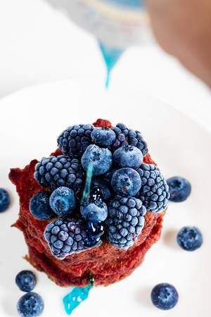 Blue topping pours on top of beetroot pancakes with blueberries and mulberries